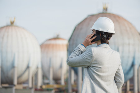 pioneer: successful independent engineer woman talking on the phone on industrial area with safety helmet showing back. Pioneer woman at work with spherical tanks. Stock Photo