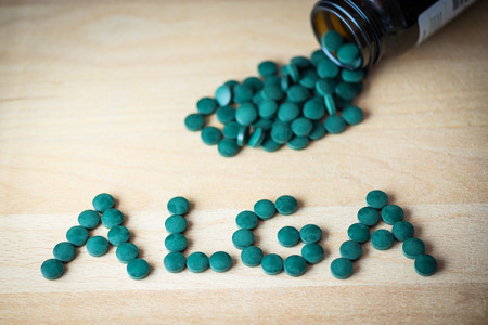 antioxidant: Spirulina supplement pills making up the word alga on wooden board and bottle. Antioxidant alga nutrition. Stock Photo