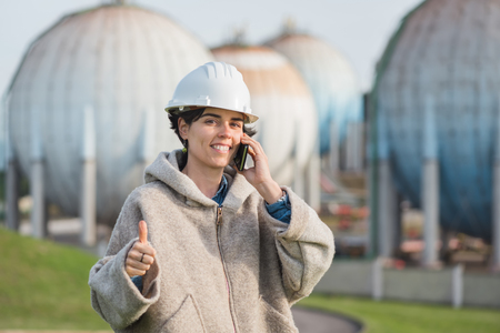 preasure: successful independent engineer smiling woman talking on the phone on industrial area with safety helmet giving thumb up. Pioneer woman at work with spherical tanks.