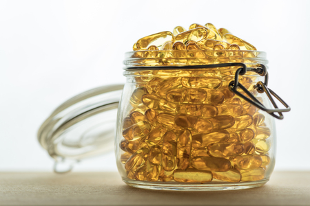 permeability: Omega 3-6-9 fish oil yellow softgels on wooden board into airtight glass jar