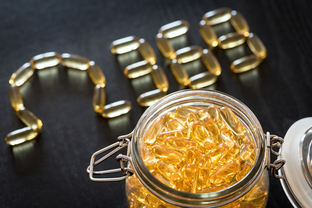 airtight: Omega 3-6-9 fish oil yellow softgels drawing omega 3-6-9  letters on wooden black table. Glass airtight jar.