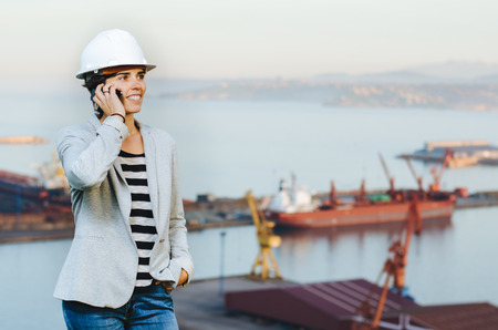 pioneer: successful independent engineer woman talking on the phone and smiling on industrial harbor with safety helmet. Pioneer woman at work. Stock Photo