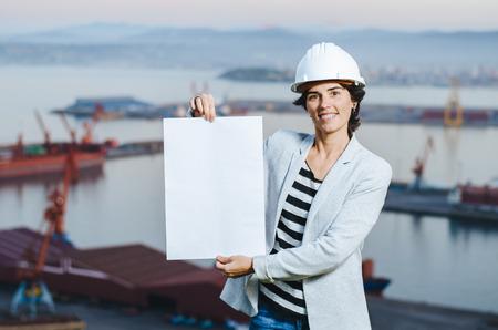 mujer trabajadora: exitosa mujer joven ingeniero independiente que muestra la tarjeta en blanco en el puerto industrial con el casco de seguridad. . mujer pionera en el trabajo. Foto de archivo