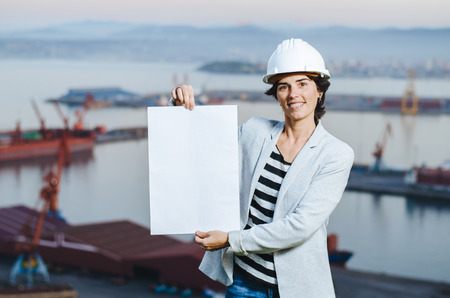 pioneer: successful young independent engineer woman showing blank board on industrial harbor with safety helmet. . Pioneer woman at work.