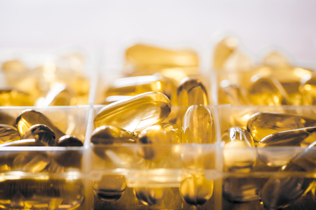 permeability: Omega 3-6-9 fish oil yellow softgels into daily pill box. Backlit detail of fat acid tablets.