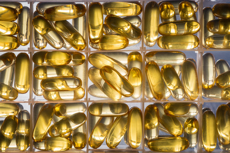 longevity medicine: Omega 3-6-9 fish oil yellow softgels into daily pill box. Backlit vertical detail of fat acid tablets.