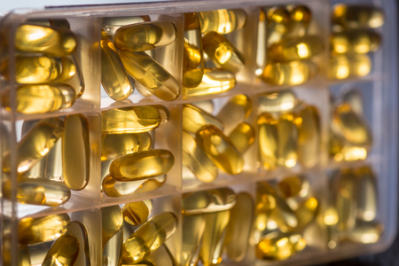 permeability: Omega 3-6-9 fish oil yellow softgels into daily pill box. Backlit vertical detail of fat acid tablets.