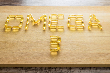 Omega 3-6-9 fish oil yellow softgels drawing omega 3 letters on wooden board on rustic table. Banco de Imagens - 57980040