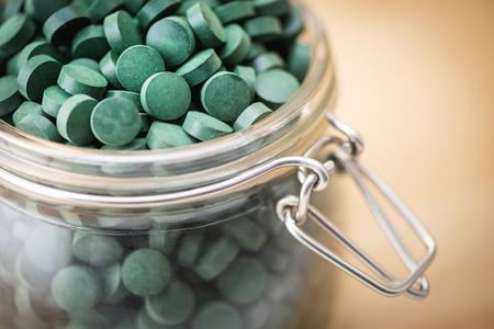 preasure: Spirulina supplement pills into airtight jar. Antioxidant alga nutrition.
