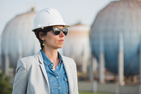 pioneer: successful independent engineer woman on industrial area with safety helmet crossing arms. Pioneer woman at work with spherical tanks.