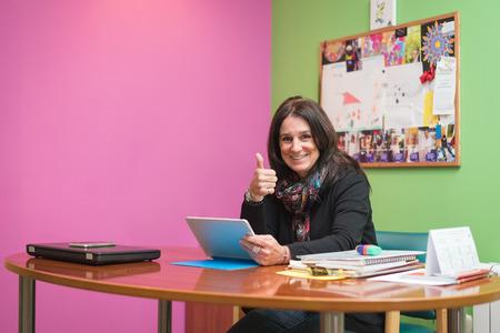 smiley pouce: smiley entrepreneur milieu professionnel ans femme brune au bureau de poste de travail avec un ordinateur portable tenant une tablette et donnant pouce vers le haut Banque d'images
