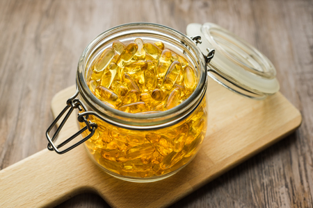 permeability: Omega 3-6-9 fish oil yellow softgels on wooden board on rustic table into airtight glass jar