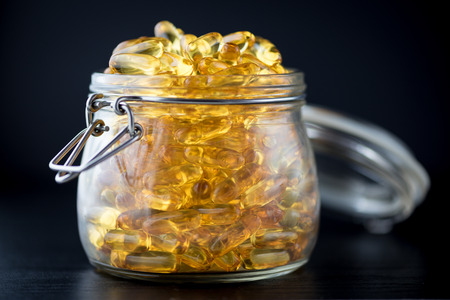 airtight: Omega 3-6-9 fish oil yellow softgels on wooden black board into airtight glass jar Stock Photo