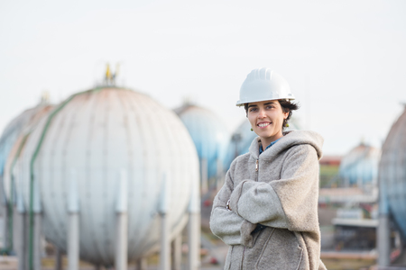 pioneer: successful independent engineer smiling woman on industrial area with safety helmet crossing arms. Pioneer woman at work with spherical tanks.