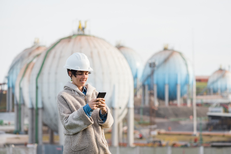 preasure: successful independent engineer woman looking at the phone and smiling on industrial area with safety helmet. Pioneer woman at work with spherical tanks.
