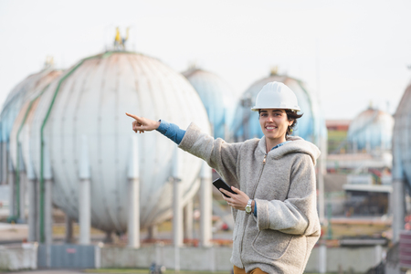 preasure: successful independent engineer woman pointing and smiling on industrial area with safety helmet and phone. Pioneer woman at work with spherical tanks.