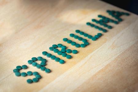 preasure: Spirulina supplement pills making up the word spirulina on wooden board. Antioxidant alga nutrition.