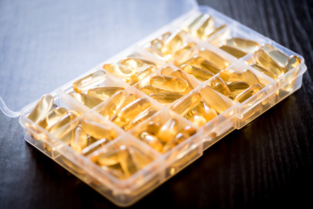 permeability: Omega 3-6-9 fish oil yellow softgels into daily pill box. Backlit closeup of fat acid tablets.