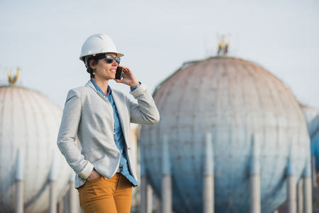 preasure: successful independent engineer smiling woman talking on the phone on industrial area with safety helmet. Pioneer woman at work with spherical tanks wearing sunglasses.