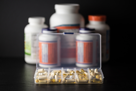 Supplements into daily pill box in front of capsules, pills, softgel and tablet bottles, on black wood table with dark background. Dietary support sort. Banco de Imagens