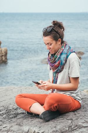 relaxed woman sitting on a rock by the sea texting on phone with sunglasses on summer