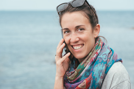 happy cheerful woman by the sea talking on phone with sunglasses on sunny day