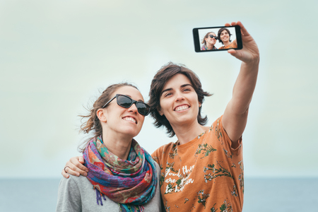 Two young women friends taking a selfie by the sea on summer. Cheerful firiends enjoying sunny day by the sea.