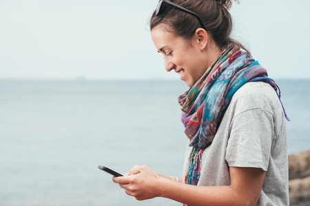cheerful smiley woman by the sea texting on phone with sunglasses on summer