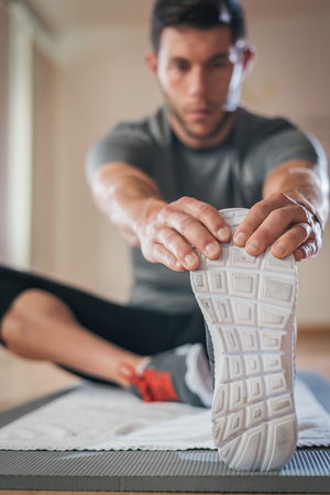 floor mat: Sporty man stretching leg before gym workout. Fitness strong male athlete on floor mat and towel warming up indoor. Stock Photo