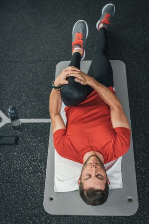 floor mat: Sporty man stretching leg before gym workout. Fitness strong male athlete on floor mat and towel warming up with bottle and cellphone.