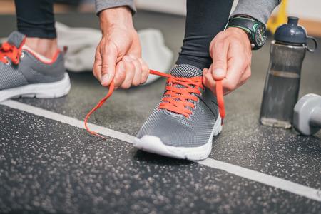 クローズ アップ靴を実行しています。ジム屋内トレーニング、フィットネス健康的な概念。スポーツを結ぶ男性アスリートのトレーニングの前にひ