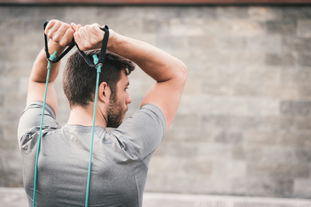 expander: urban fitness man looking aside while working out  triceps using expander. Sporty strong male exercising outdoors with elastic straps. Stock Photo