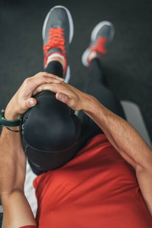 floor mat: healthy man stretching leg before gym workout. Fitness strong male athlete on floor mat and towel warming up with bottle and cellphone.