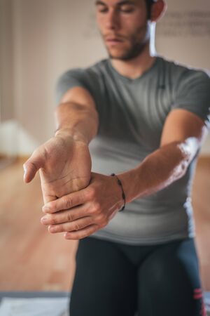 forearm: Sporty man stretching forearm before gym workout. Fitness strong male athlete standing indoor warming up.