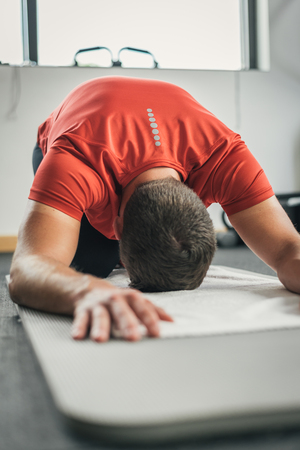 floor mat: Sporty man stretching back before gym workout. Fitness strong male athlete on floor mat and towel warming up indoor. Stock Photo