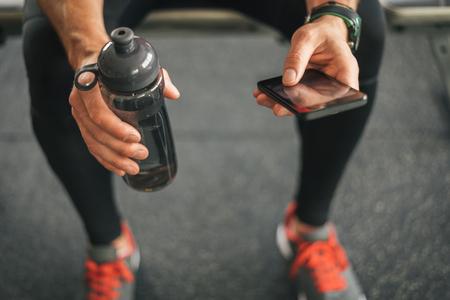 Fitness homme regardant vers le téléphone pour la motivation avant séance de gym. mâle sportif athlète regardant son smartphone tenant une bouteille d'eau.
