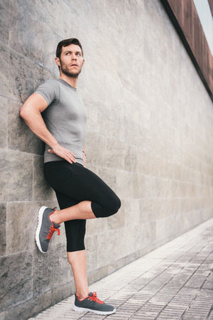 strenght: urban fitness man looking aside while resting leaning on wall. Sporty strong male exercising outdoors.