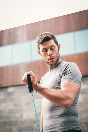 urban fitness man looking at his biceps while working out using expander. Sporty strong male exercising outdoors with elastic straps. Stock Photo