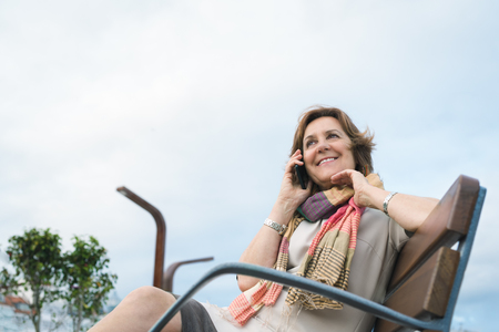 smily: Smily mature woman talking on phone while sitting on a bench outdoor. Modern urban woman confidence concept.