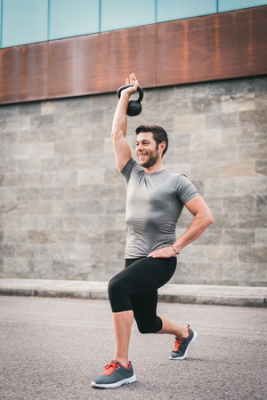 Sporty man exercising with kettlebell on urban outdoor workout. Fitness smily man working out outside.