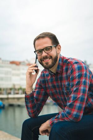 Smiling bearded man phoning while sitting at leissure harbor. Urban maritime vacations lifestyle.