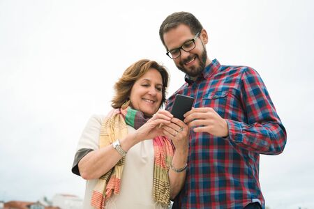 Smiling Mother and son using smartphone showing pictures. Urban maritime vacations on summer.