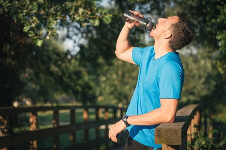 Runner man drinking water from bottle while resting during outdoor training workout. Fit fitness sport model leaning on wooden railing.