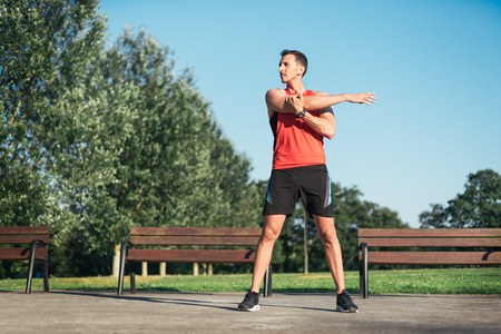 Fitness man stretching arm shoulder before outdoor workout. Sporty male athlete in an urban park warming up. Banco de Imagens