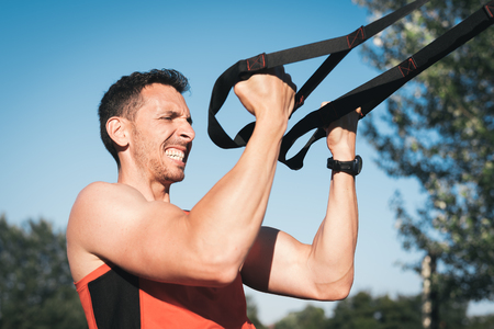 Man training arms with trx fitness straps outdside. Workout healthy lifestyle sport concept.