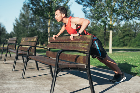 Sports man doing push-ups during outdoor cross training workout. Fit fitness sport model training outside using street furniture.