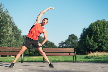 Fitness man stretching body before outdoor workout. Sporty healthy male athlete in an urban park warming up.