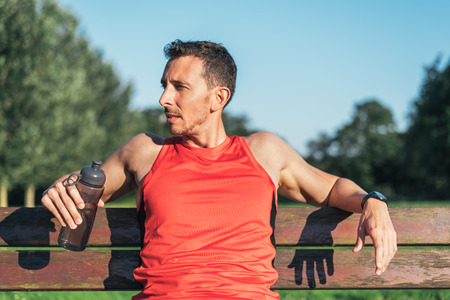 Fitness man resting during outdoor cross training workout with water bottle. Fit fitness sport model sitting on a bench outside using street furniture. Banco de Imagens