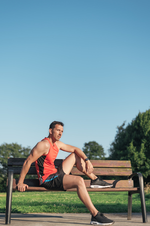 Fitness man resting during outdoor cross training workout. Fit fitness sport model sitting on a bench outside using street furniture. Banco de Imagens