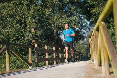 Male runner running in urban park.  strong man athlete exercising outdoor.